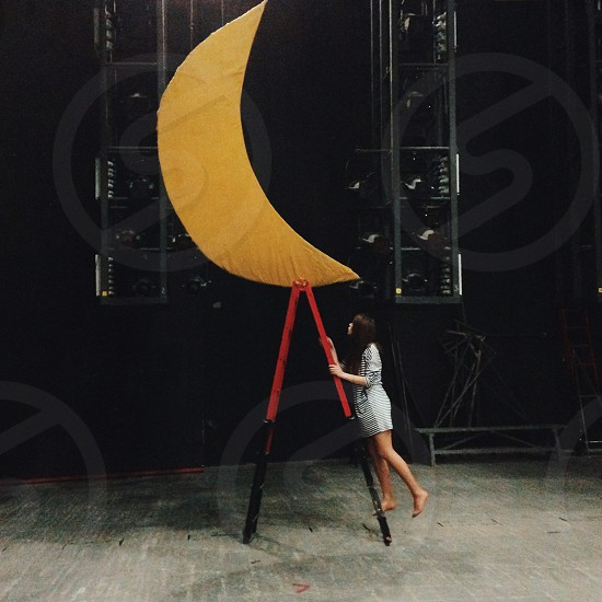 woman in blue jacket and gray skirt climbing red and black ladder while facing moon cutout photo