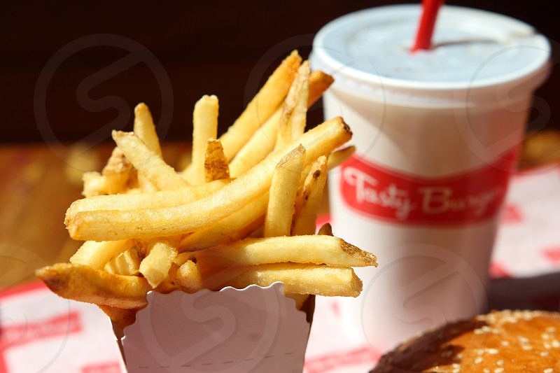 french fries on white cardboard box beside tasty burger drink photo