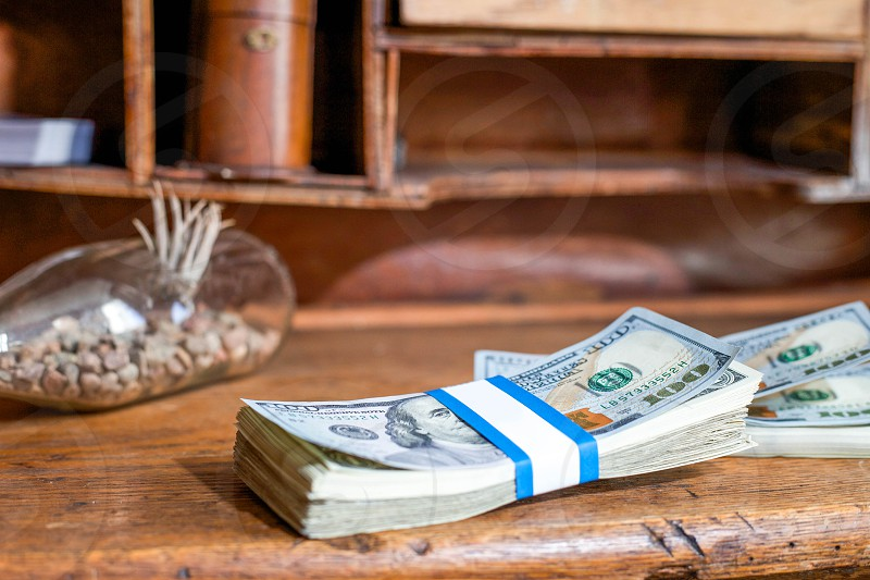 bundle of 100 u.s dollar bill on brown wooden desk photo