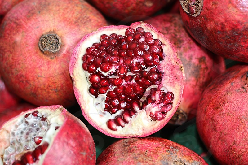 Ariel view of the inside of a pomegranate on a pile of pomegranates photo