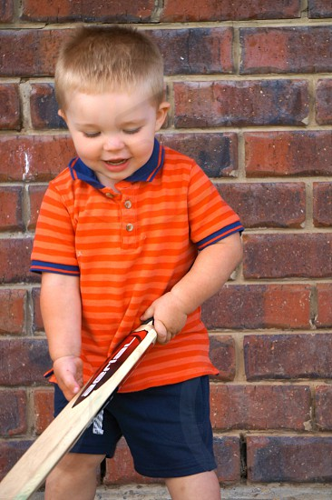 boy in orange striped polo shirt holds brown cricket bat photo