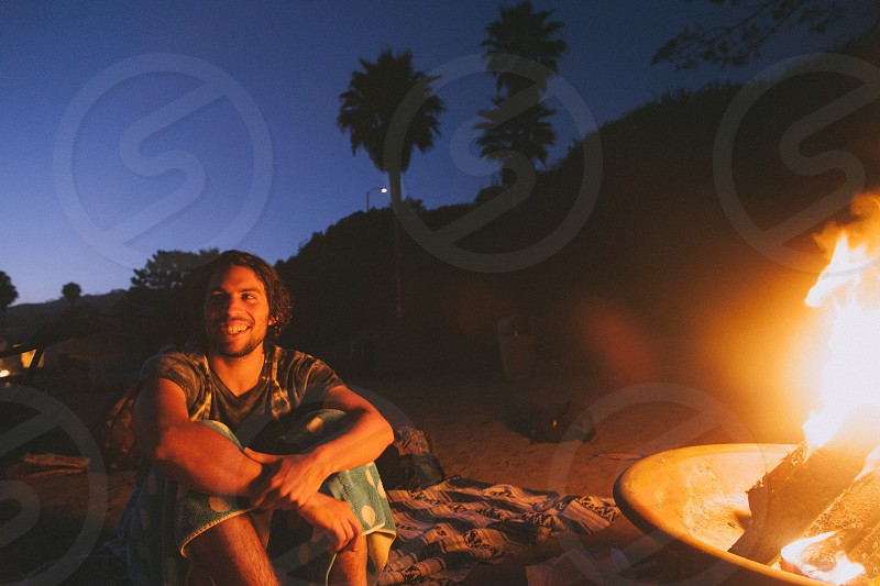 man sitting in front of fire pit photo