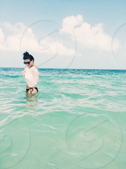 woman in black bikini with white cover up standing on the sea during day time photo