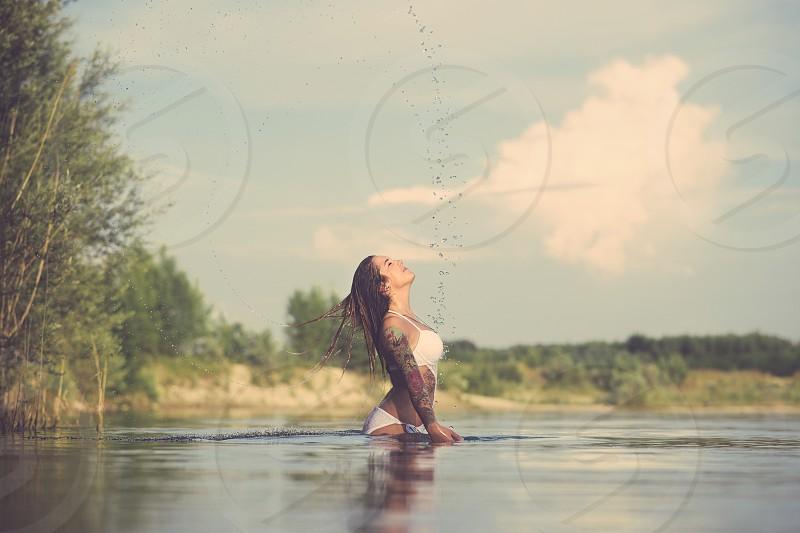 Young Tattooed Woman Splashing Lake Water on a Summer Day photo