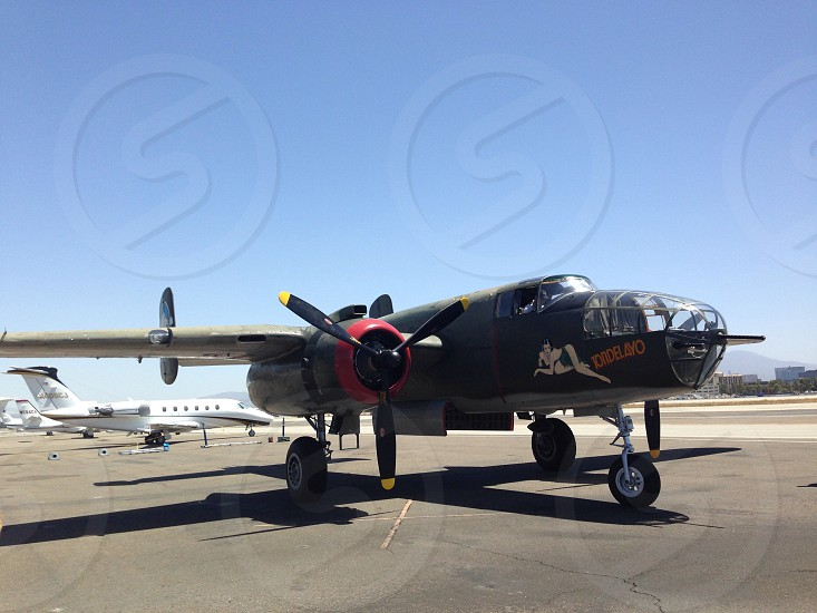 black and brown bomber plane on airfield under clear sky during daytime photo