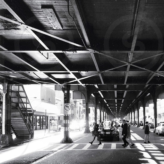 grayscale photo of people crossing street under bridge photo