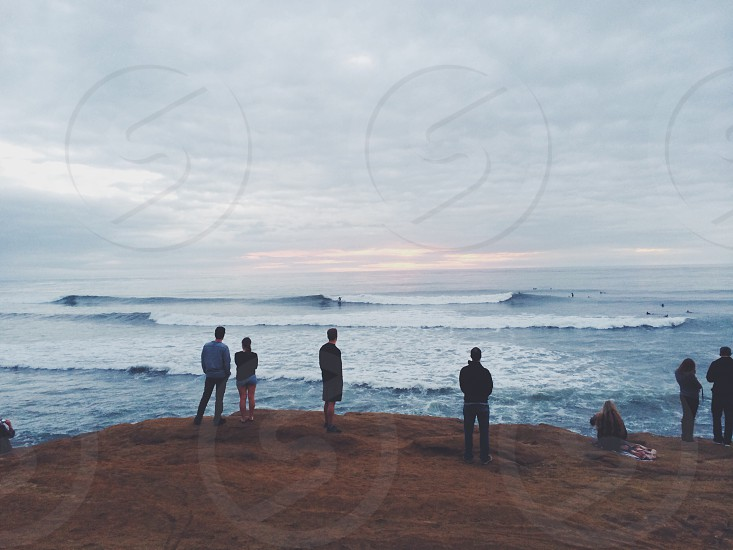 people standing on the seashore photo