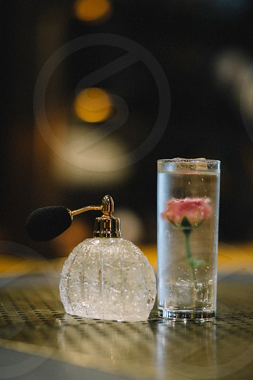 clear cut glass cologne spray beside pink rose flower inside a clear drinking glass with ice cubs photo