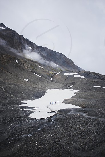 four people climbing a mountain with white snow patches under a cloudy sky photo