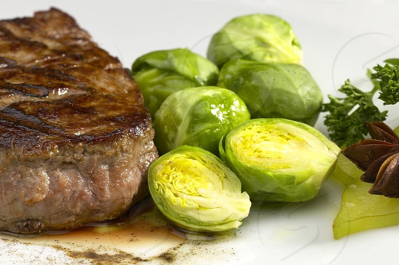 juicy filet mignon on plate with brussel sprout photo