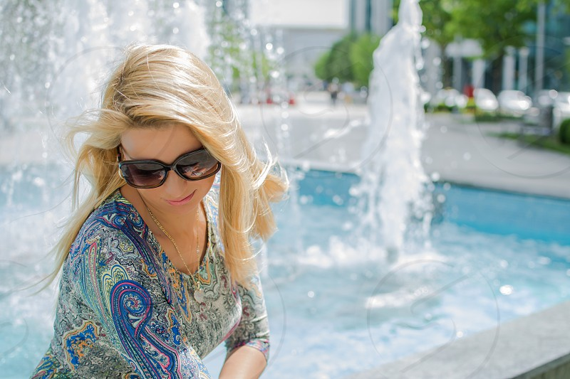 Beautiful young woman with long blond hairblack glasses and colorful dress outdoor near blue fountain photo