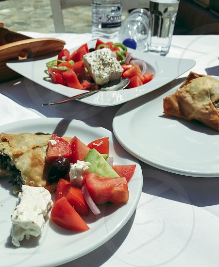 Greek food vacation Greek salad feta cheese vegetables dish pie food on the table  outdoors restaurant photo