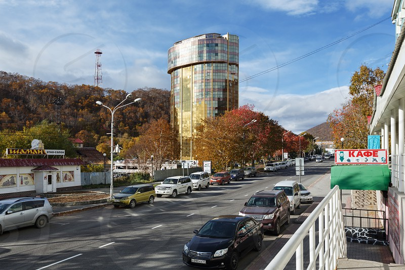 PETROPAVLOVSK-KAMCHATSKY KAMCHATKA PENINSULA RUSSIA - OCT 12 2016: Autumn cityscape - view of center of city Petropavlvosk-Kamchatsky Leninskaya Street modern skyscraper and road with parked cars photo