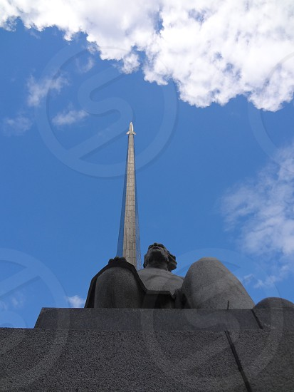 """Konstantin Tsiolkovsky a Russian rocket pioneer sits in front of the """"Monument to the Conquerors of Space"""" in Moscow Russia photo"""