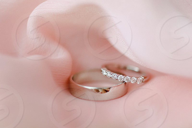silver wedding rings on pale pink fabric  photo