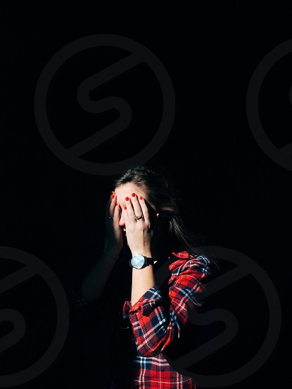woman in red blue and white plaid dress shirt covering her eyes with her hands photo
