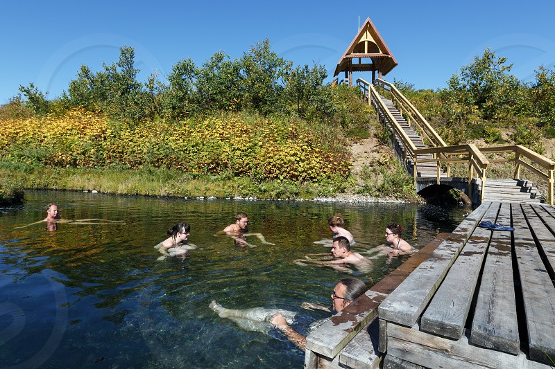 NALYCHEVO NATURE PARK KAMCHATKA PENINSULA RUSSIA - SEP 7 2013: Group hot springs in Nalychevo Nature Park - tourists take a therapeutic (medicinal) baths in pool with natural thermal mineral water having balneological properties. photo