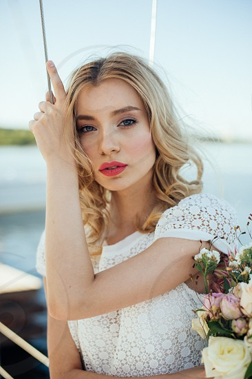 Portrait of beautiful bride with flowers in her hands at the yacht in the lake photo