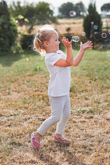 Little girl playing with soap bubbles outdoors on summer day. Real people authentic situations photo