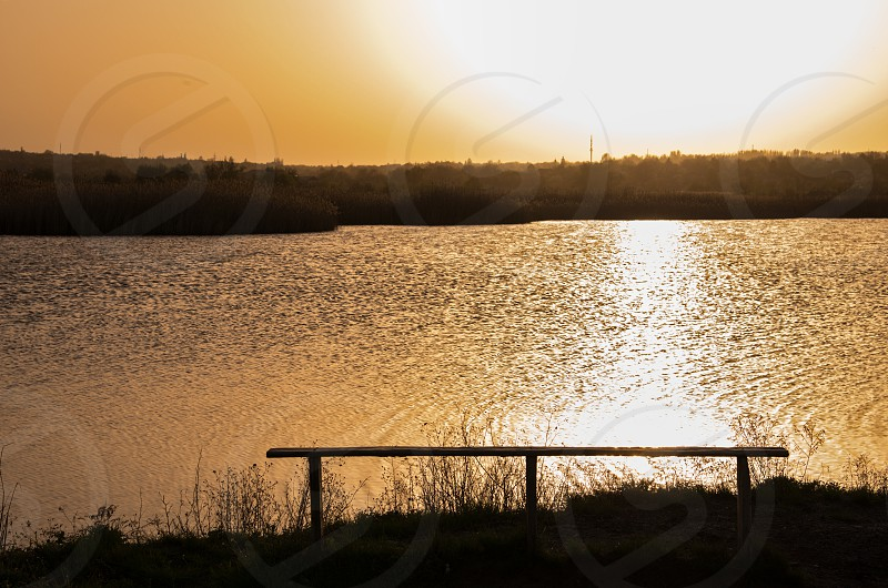 Sunset under the water space with empty bench photo