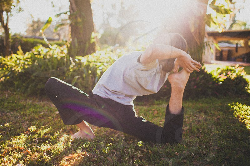 woman with brown hair wearing white shirt and black pants doing yoga on green field photo