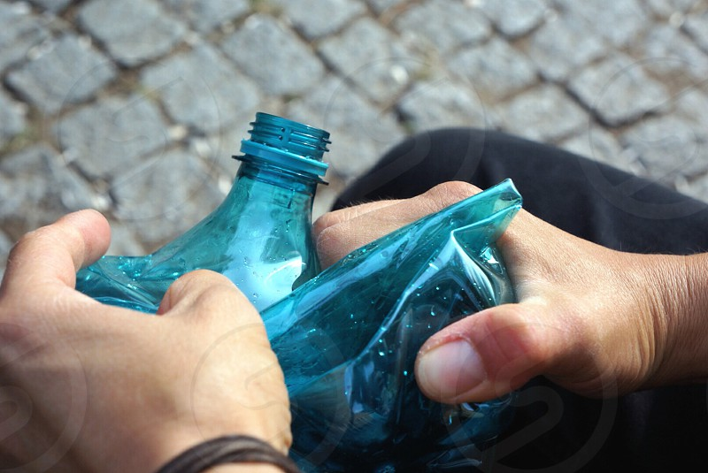 person holding a crushed blue soda bottle photo