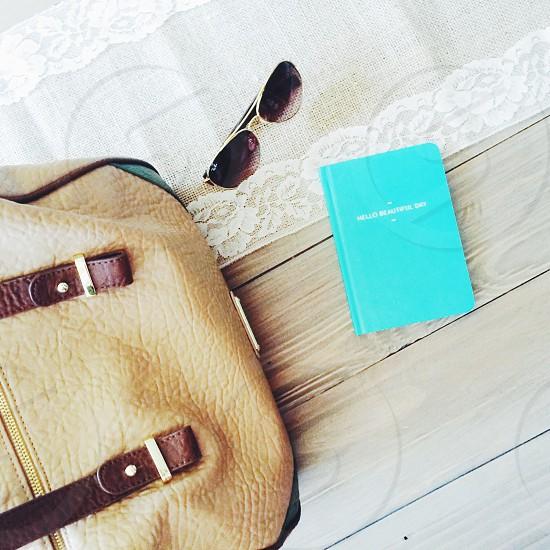 brown leather bag beside green hardbound book photo