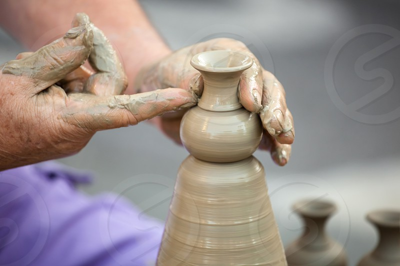 Close up of hands making pottery on a wheel photo