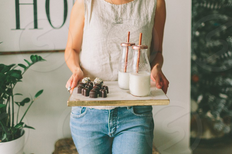 A woman preparing a beautiful tray of chocolates and milk. photo