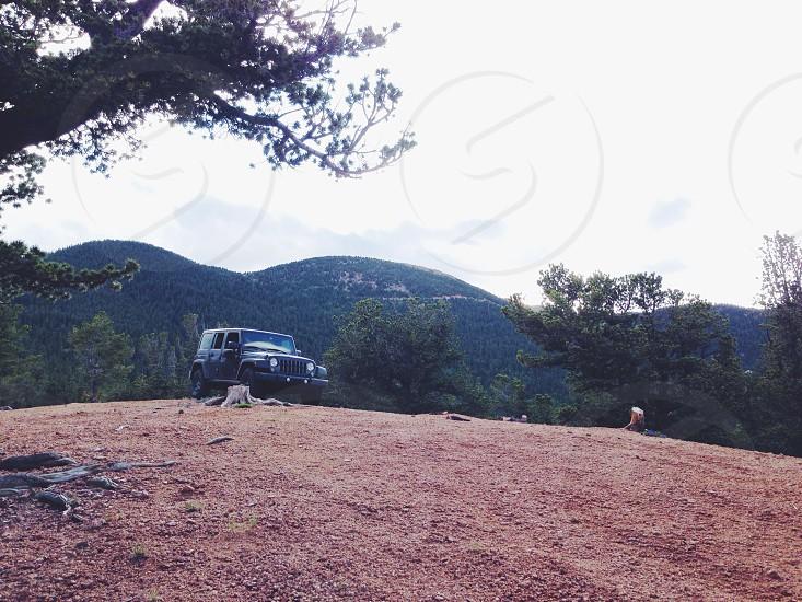 black Jeep Wrangler on hill top photo