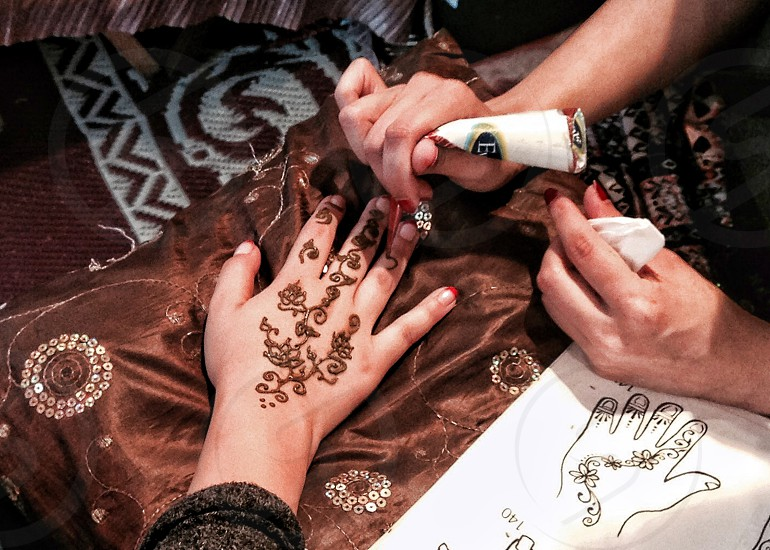Henna design is being applied to a hand in an aerial view photo