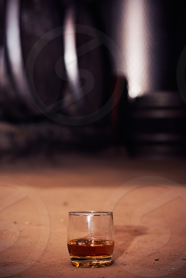 Glass of scotch neat without ice on the floor at distillery wooden and metal barrels in the background. photo