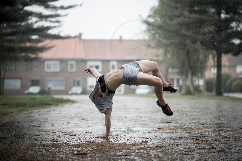 woman in a back flip in the rain photo