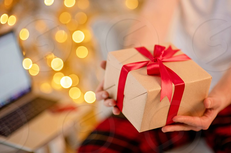 Adult man holds a gift for advent holiday on a laptop background. Makes online purchases. Happy New Year and Merry Christmas photo