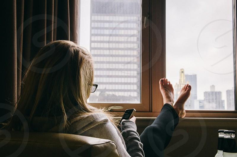 woman using mobile phone sitting next to window photo