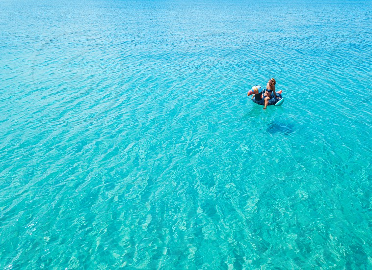 Aerial view of woman floating on the water mattress in the turquoise sea photo
