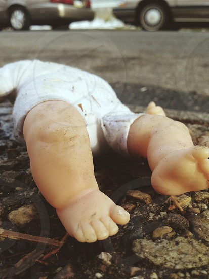 beige plastic doll on ground photo