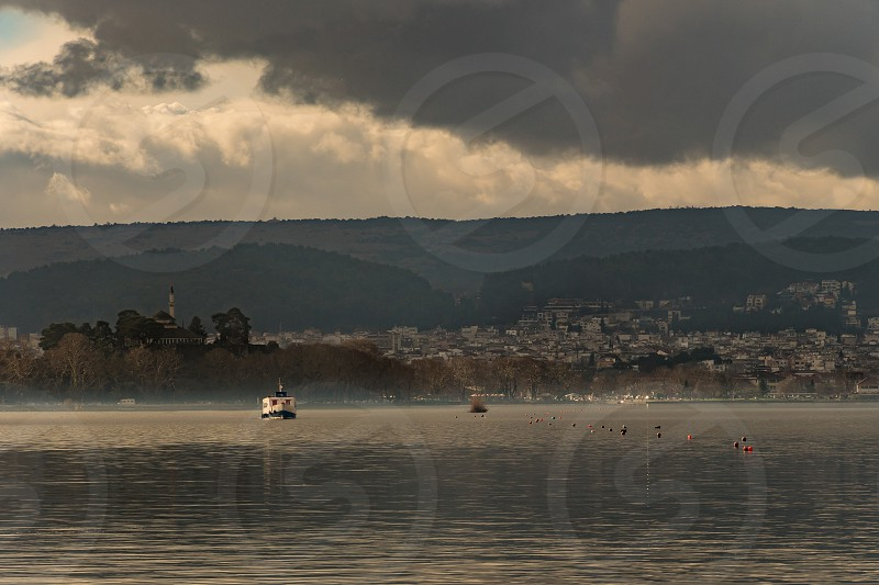 View of Ioannina city and the castles' s minaret from the pamvotida lake in Ioannina Greece photo