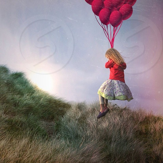 gild holding red balloon photo