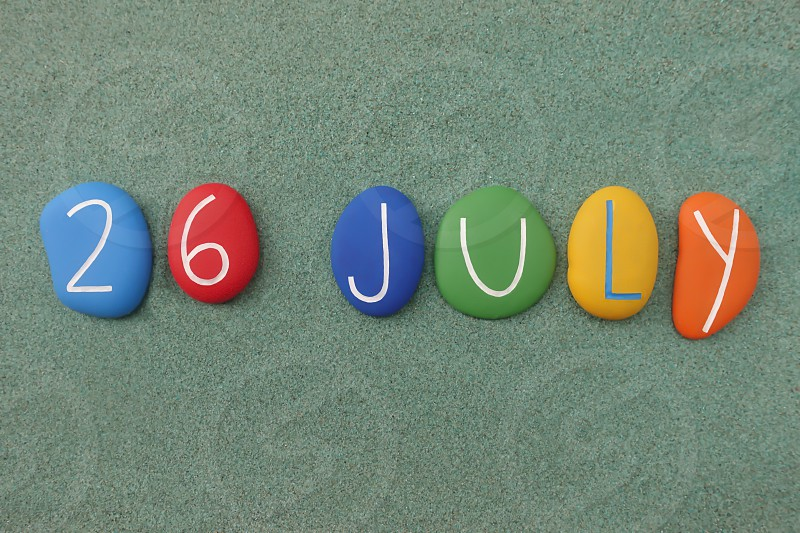 26 July calendar date composed with multi colored stones over green sand                      photo