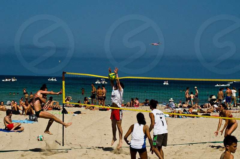 people on beach playing volleyball photo