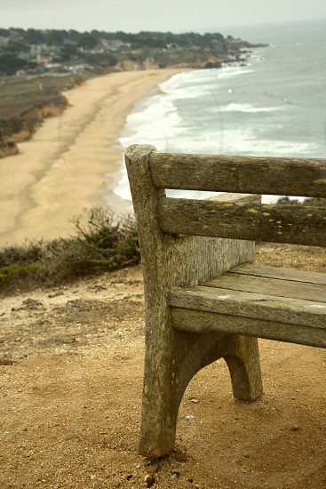weathered bench on cliffs overlooking ocean photo