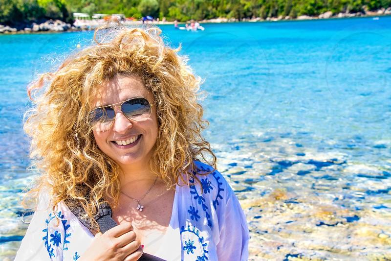 woman wearing aviator sunglasses smiling near body of water during daytime photo
