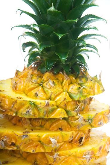 ripe vivid pineapple sliced over white background photo