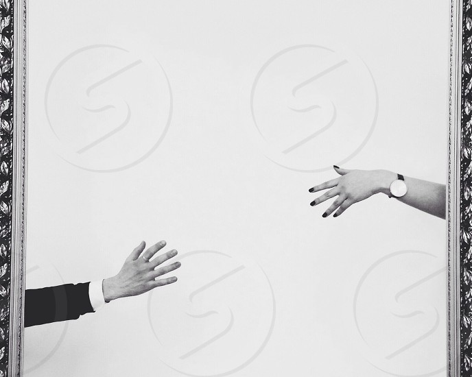 person wearing suit and another person wearing round watch reaching each other's hand in grayscale photography photo