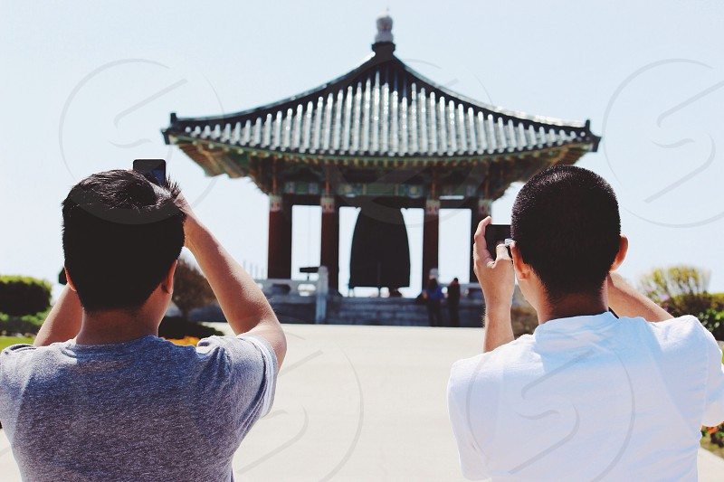 two men taking a photo of asian temple  photo