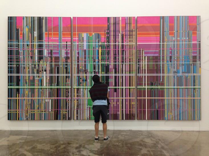 man facing multicolored wall art photo