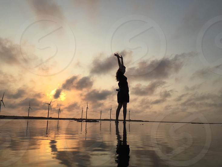 silhouette of woman on body of water during golden hour photo
