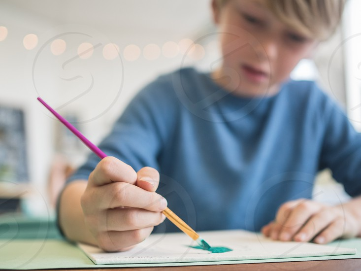 A boy painting with a brush in a classroom.  photo