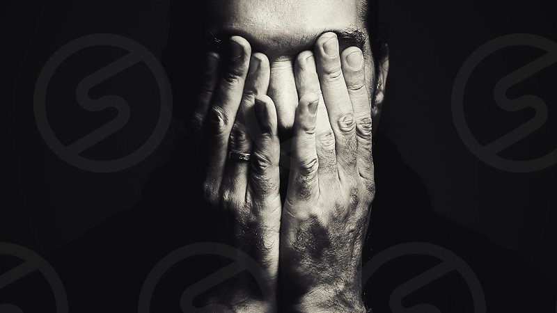 Portrait of a man with hands on face depressed expression in black and white. photo